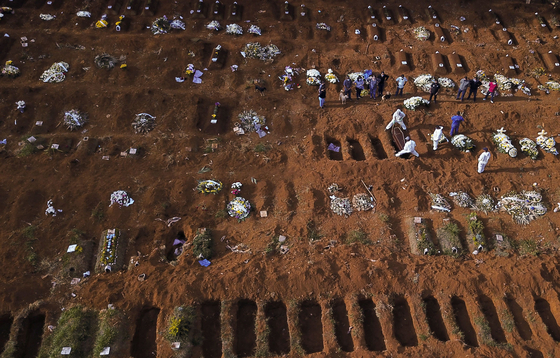 상브라질 최대의 공원묘지에서 방호복을 입은 묘지 인부가 신종 코로나바이러스 감염증(코로나19) 희생자를 묘지에 안장하고 있다. [로이터=연합]