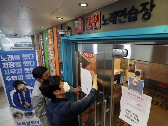 신종 코로나바이러스감염증(코로나19) 확산을 우려해 서울시가 모든 코인노래방에 대해 사실상 영업중단을 명령한 22일 서울 종로구의 한 코인노래방 입구에 종로구청 관계자들이 집합금지안내문을 붙이고 있다. [뉴스1]