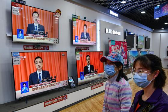 22일 중국 베이징의 한 가전제품 매장내 TV에서 리커창 중국 총리의 전인대 정부 업무 모습이 생중계되고 있다.[AFP=연합뉴스]