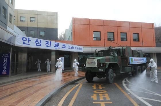 지난 3월 4일 서울성모병원 안심진료소 앞에서 서초구청 관계자와 국군화생방호사령부 소속 군인들이 선별진료소 방역 작업을 하고 있다. 연합뉴스