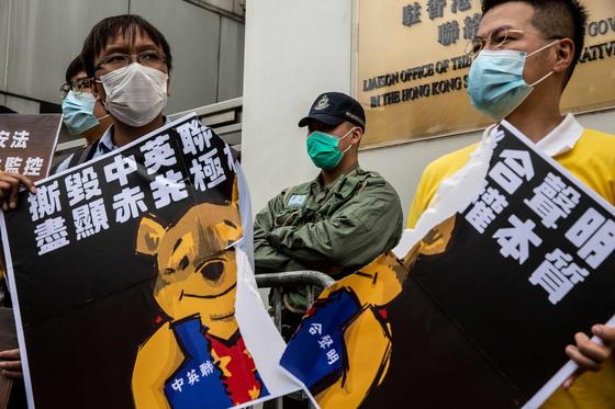 마이크 폼페이오 미국 국무장관이 홍콩 국가보안법 제정을 강행할 경우 홍콩 특별지위 박탈을 경고한 가운데 홍콩의 시위대가 24일 중앙정부 연락사무소 앞에서 '일국양제'보장을 담은 '중영 공동 성명'을 파기했다고 적은 플래카드를 찢으며 시위를 벌이고 있다.[AFP=연합뉴스]