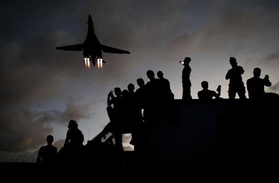 지난 21일 괌의 앤더슨 공군기지에서 비행 중인 B-1B 랜서를 배경으로 정비요원이 셀카를 찍고 있다. [미 공군]