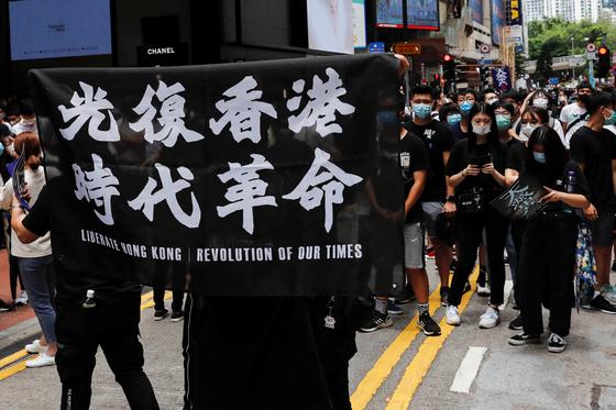 중국이 홍콩 국가보안법을 제정하겠다고 나선 가운데 홍콩에서 이에 반대하는 시위가 24일 열렸다. 한 시위자가 '광복 홍콩, 시대 혁명'이라는 글귀가 새겨진 천을 들고 있다. [로이터=연합뉴스]
