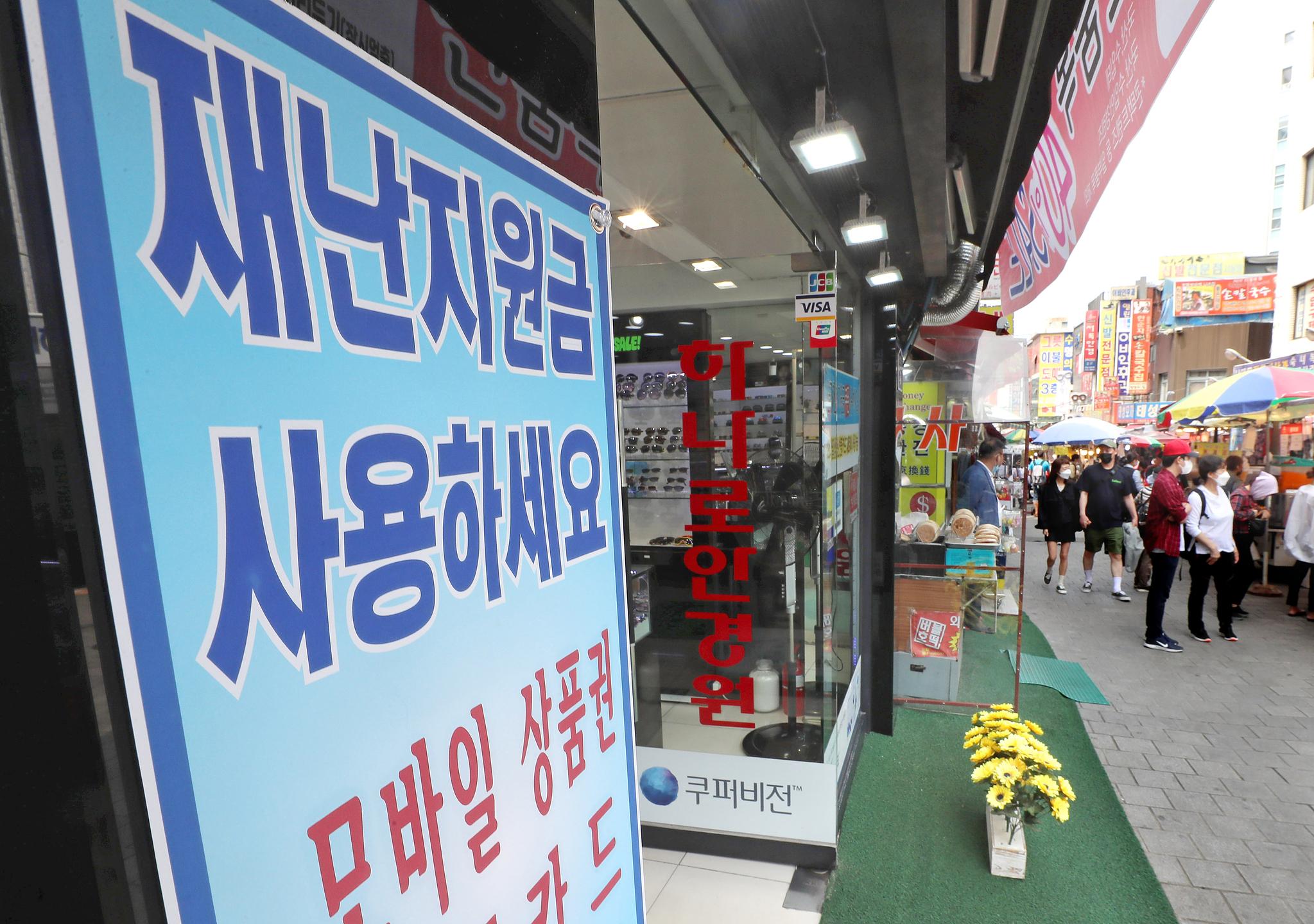 서울 중구 남대문시장 한 상점에 긴급재난지원금 사용 가능 안내문이 붙어 있다. 연합뉴스