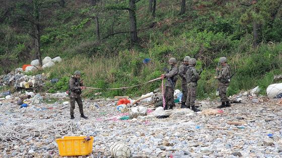 중국에서 밀입국한 것으로 추정되는 소형보트가 발견된 충남 태안군 소원면 해안가에서 25일 오전 군 장병이 정리 작업을 하고 있다. 신진호 기자