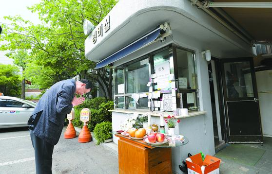 지난 11일 서울 우이동의 한 아파트 경비실 앞에 차린 분향소에서 한 주민이 숨진 경비원을 애도하고 있다. 뉴스1