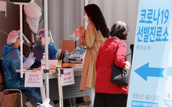 20일 서울 영등포구청 선별진료소에서 한 시민이 검사를 받기 위해 안내를 받고 있다. 뉴스1
