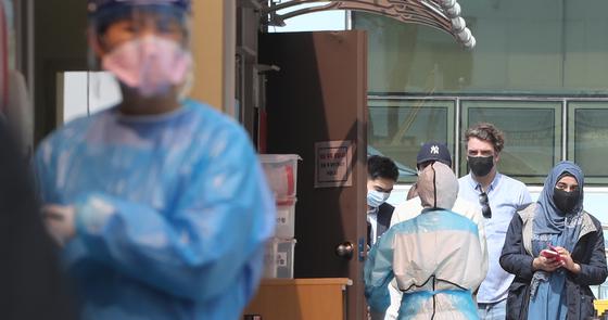 지난 11일 오전 용산구 순천향대병원 선별진료소에서 외국인들이 검사를 기다리고 있다. 연합뉴스