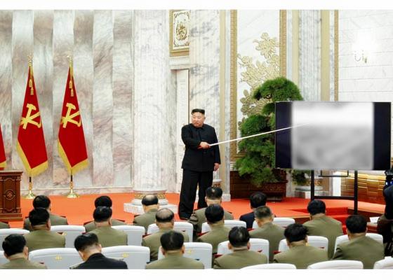 북한 매체들이 24일 보도한 당 중앙군사위원회 확대회의에서 김정은 국무위원장이 2m 가량의 지휘봉으로 스크린을 가리키며 군 간부들에게 지시하고 있다. 스크린 내용은 노출을 피하기 위해 모자이크 처리됐다. [연합뉴스]