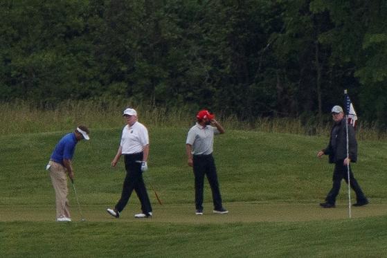 미국 경제 재개를 축하하는 의미에서 도널드 트럼프 미 대통령이 24일(현지 시간) 마스크를 착용하지 않고 골프를 즐기고 있다. [로이터=연합뉴스]