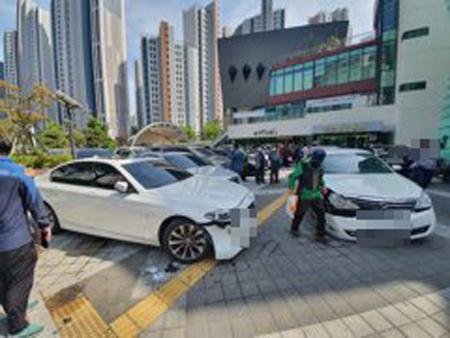 지난 23일 오후 2시 40분께 부산 남구 부산예술회관 주차장에서 60대 운전자가 후진 중 보행자를 치고 주차된 BMW, 벤츠, 에쿠스, 혼다 등 차량 4대를 잇달아 들이받은 후 멈춰있다. 사진 부산경찰청