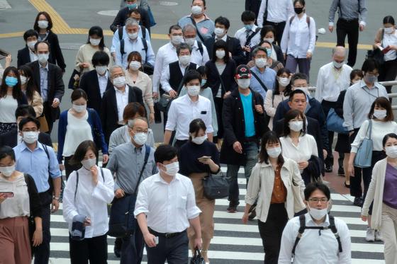 일본 도쿄에서 코로나19 긴급사태가 해제된 다음 날인 26일, 마스크를 쓴 시민들이 도쿄 시내를 지나고 있다. [AFP=연합뉴스]
