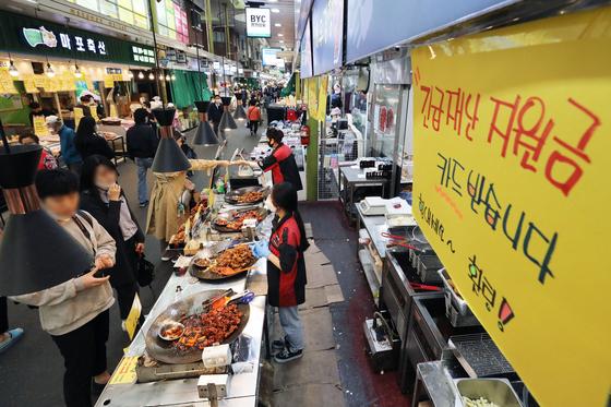 19일 오후 서울의 한 전통시장 긴급재난지원금 카드 사용가능 매장에 안내문이 붙어 있다. 뉴스1