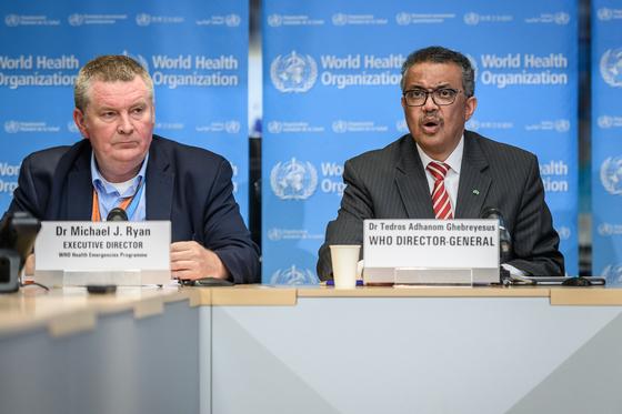 마이클 라이언 WHO 긴급준비대응 사무차장(왼쪽)과 테워드로스 아드하놈 거브러여수스 WHO 사무총장(오른쪽)이 3월 11일 스위스 제네바에서 열린 코로나19 브리핑에 참석한 모습. [AFP=연합뉴스]