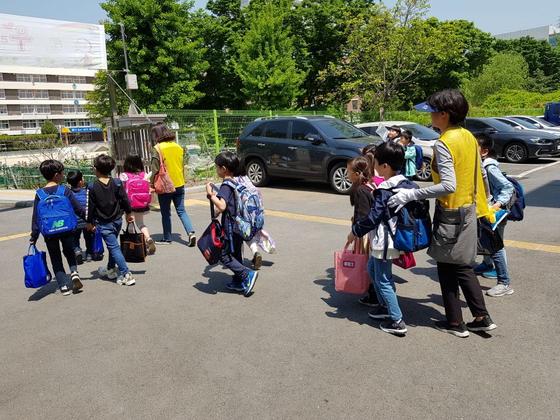 강동구는 등교 개학에 맞춰 6월부터 교통안전지도사가 수업을 마친 초등학교 1~2학년 학생을 집까지 안전하게 데려다주는 '워킹 스쿨버스'를 운영한다. [사진 강동구]