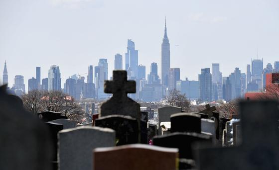 미국 뉴욕 브루클린에 있는 한 공동묘지 뒤로 맨해튼 고층빌딩이 보인다. 미국은 27일(현지시간) 코로나19로 인한 사망자가 10만 명을 넘었다. 첫 사망자가 보고된 지 3개월 만이다. [AFP=연합뉴스]