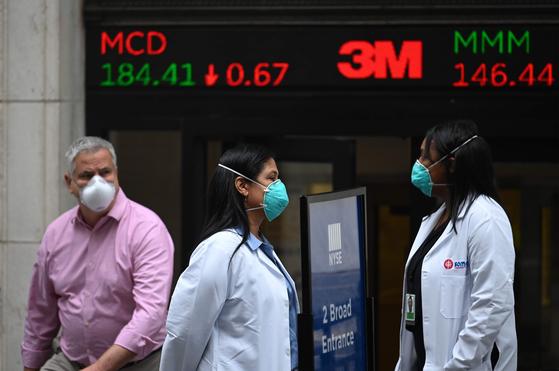 26일 미국 뉴욕 월스트리트 증권거래소 앞에서 시민과 의료진이 마스크를 쓴 채 걸어가고 있다.[AFP=연합뉴스]