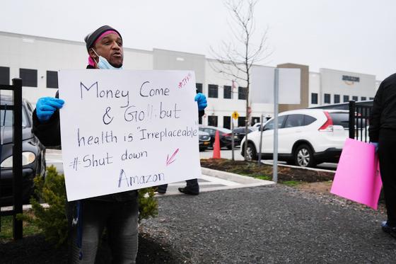 뉴욕 아마존 물류센터에서 한 직원이 코로나19 감염 위험에서 직원을 보호해 달라는 팻말을 들고 있다. AFP=연합뉴스.