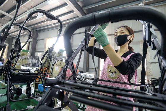 지난달 중국 허베이성 한단시의 한 유모차 공장에서 직원이 조립 공정을 하고 있다.[AFP=연합뉴스]