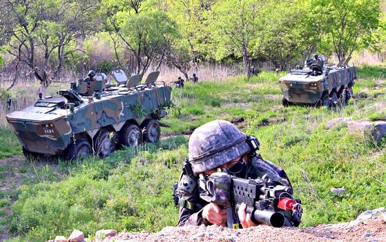 지난 21일 차륜형장갑차에서 하차한 25사단 만월봉대대 장병이 대항군 진영을 기습해 점령하고 있다. 육군은 18일부터 29일까지 강원도 홍천 육군과학화훈련단(KCTC) 훈련장에서 'Army TIGER 4.0' 보병대대 전투실험을 했다. [박용한기자]