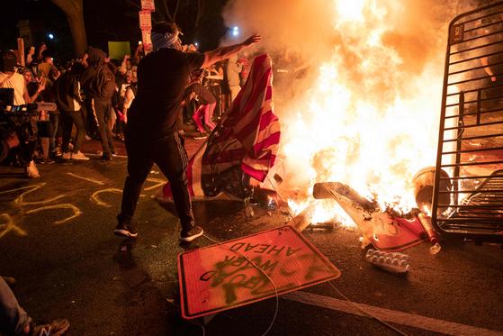 지난달 31일(현지시간) 미국 워싱턴 백악관 근처에서 시위대가 성조기를 불길속에 던져넣고 있다. 백인 경찰에 의한 흑인 사망 사건과 관련한 시위가 워싱턴에서 사흘째 열렸다.[AFP=연합뉴스]