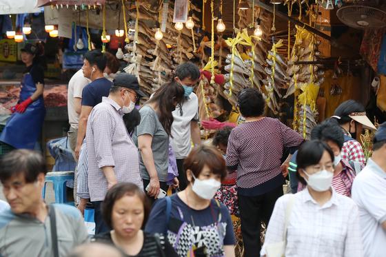 정부가 1일 문재인 대통령 주재로 비상경제회의를 열고 하반기 경제정책방향을 발표했다. 소비 진작과 관광 회복을 통해 신종 코로나바이러스 감염증(코로나19)로 어려움을 겪는 경제를 회복하겠다는 방침이다. 사진은 지난 31일 서울 동대문구 경동시장이 장을 보러나온 시민의 모습. 뉴스1
