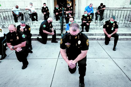 경찰의 과도한 무력 사용으로 흑인 남성 조지 플로이드가 사망한 뒤 시위가 미 전역으로 번지자 경찰관들도 시위 현장에서 한쪽 무릎을 꿇는 것으로 추모의 뜻을 표하고 있다. 사진은 플로리다주 코럴 게이블스의 경찰관들. [AFP=연합뉴스]