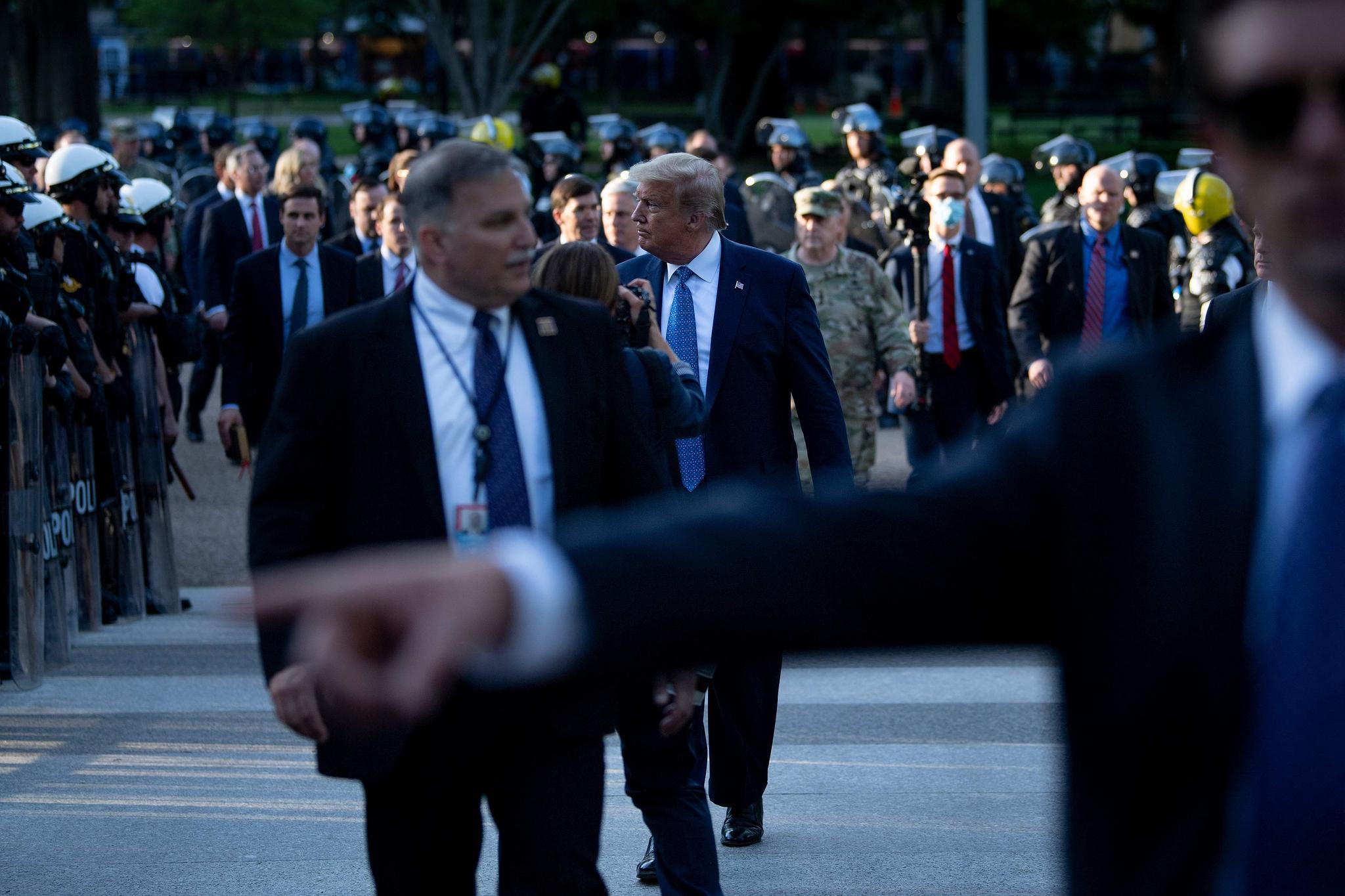 도널드 트럼프 미국 대통령이 1일(현지시간) 세인트 존스 교회를 방문한 뒤 진압복을 입은 경찰 사이를 지나 백악관으로 복귀하고 있다. [AFP=연합뉴스]