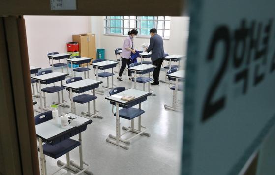 3차 등교 수업(고1·중2·초3~4학년)을 하루 앞둔 2일 서울 구로구 항동중학교 2학년 교실에서 교사들이 학생들에게 제공할 손소독제와 마스크를 책상에 올려 놓고 있다. 뉴스1