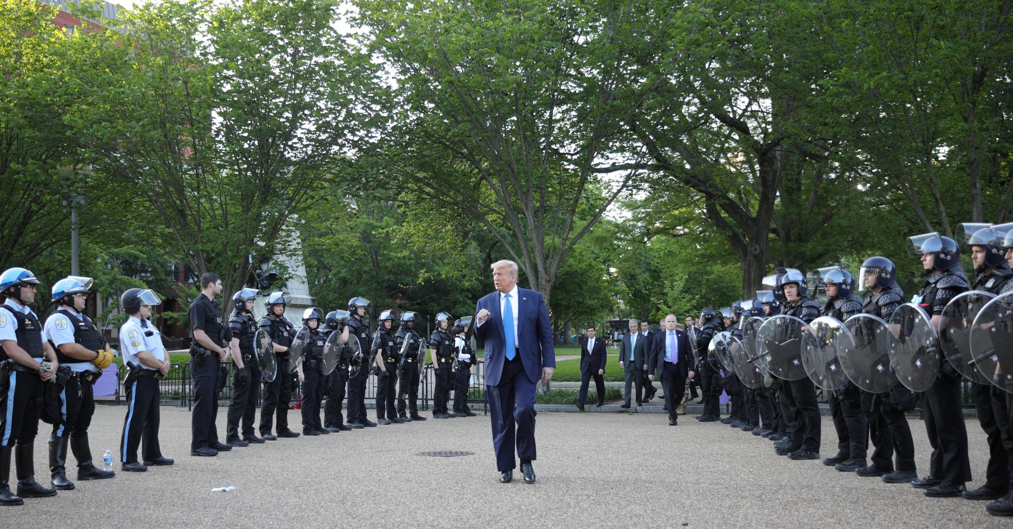도널드 트럼프 대통령이 1일(현지시간) 백악관을 나와 세인트존스 교회로 가는 도중 진압복을 입은 경찰 사이를 지나며 주먹을 쥐어 보이고 있다. [로이터=연합뉴스]