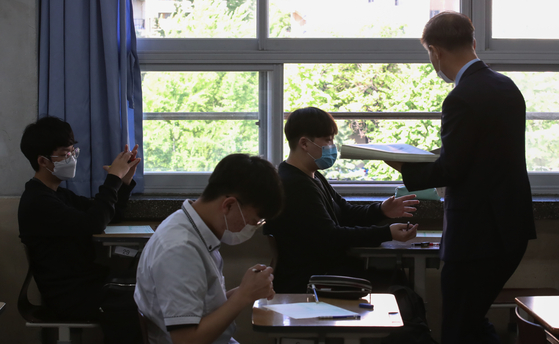 전국연합학력평가가 시행된 지난달 21일 오전 서울의 한 고등학교에서 선생님이 문제지를 나눠주고 있다. 연합뉴스