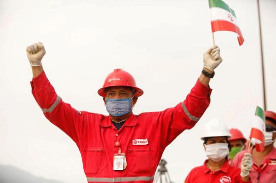 지난달 25일 휘발유를 선적한 이란 유조선이 베네수엘라 엘팔리토 정유시설에 도착하자 베네수엘라 국영석유회사인 PDVSA의 직원이 이란 국기를 들고 환영하고 있다. [로이터=연합뉴스]