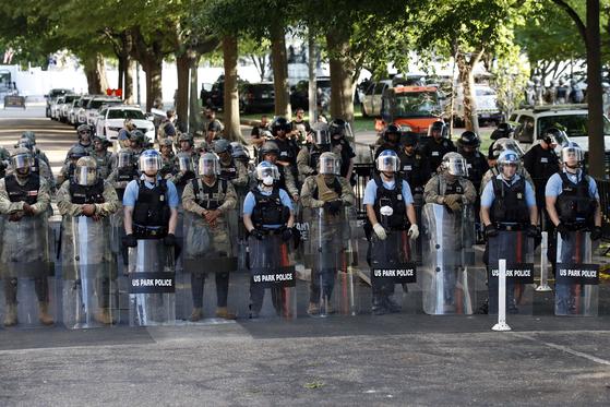 미국 워싱턴DC 주 방위군과 연방 공원 경찰, 백악관 비밀경호국 요원들이 2일 백악관 앞 라파에트 광장에서 시위대쪽을 바라보고 있다. [AP=연합뉴스]