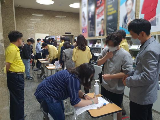 2일 서울 강남구 대치동의 A학원 입구에서 교육부 관계자와 취재진들이 문진표를 작성하고 있다. 남궁민 기자