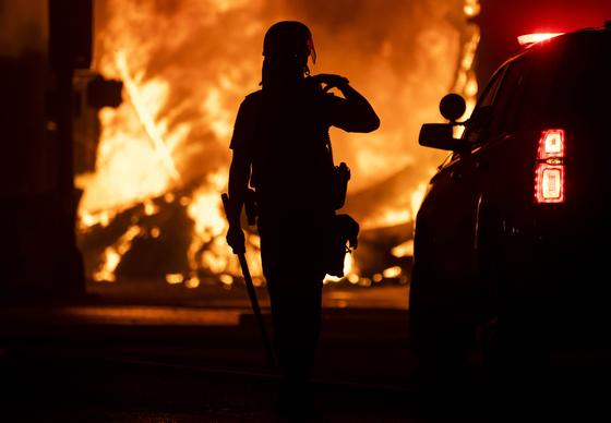 지난 28일 미 미네소타 주 미니애폴리스에서 약탈당한 전당포를 바라보는 한 경찰의 모습. AFP=연합뉴스