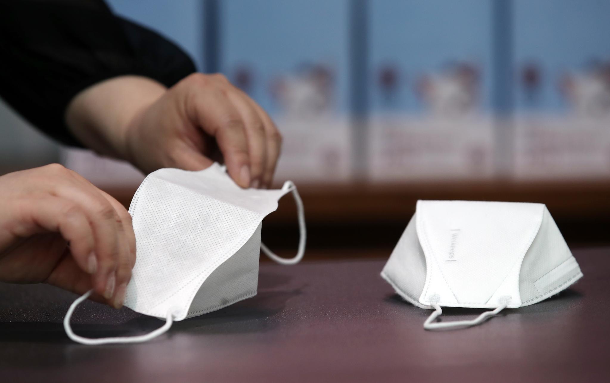 마스크 업체 웰킵스 직원이 5일부터 개당 500원에 판매된 비말 차단용 마스크(왼쪽) 샘플을 KF94 마스크(오른쪽)와 비교해 보여주고 있다. 연합뉴스