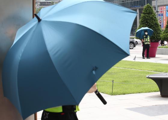 광화문 광장에서 햇빛을 가리는 우산을 쓰고 근무하는 경찰들. 주말 서울과 수도권은 강한 햇볕과 함께 뜨거운 공기가 들어오면서 낮 최고 31도까지 치솟을 것으로 보인다. 연합뉴스