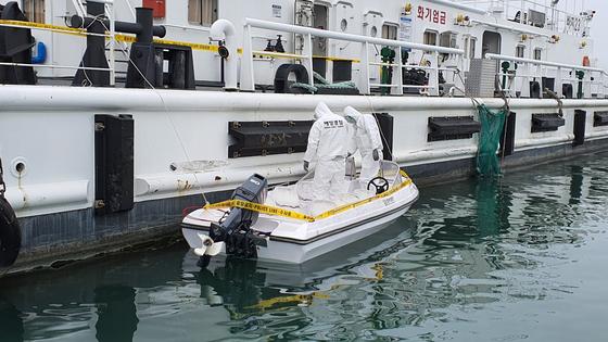 지난 25일 충남 태안군 근흥면 신진항 태안해경 전용부두에서 해경 관계자들이 전날 소원면 의항리 해변에서 발견한 소형 보트를 감식하고 있다. 신진호 기자