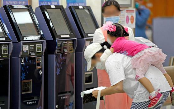9일 오후 서울 영등포구 여의도성모병원을 찾은 보호자가 마스크를 쓰고 수납업무를 보고 있다. 중앙포토