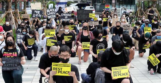 6일 오후 서울 명동에서 열린 '조지 플로이드' 사건 추모 행진 집회에서 참가자들이 행진을 마친 뒤 플로이드를 추모하며 무릎을 꿇고 있다. /연합뉴스