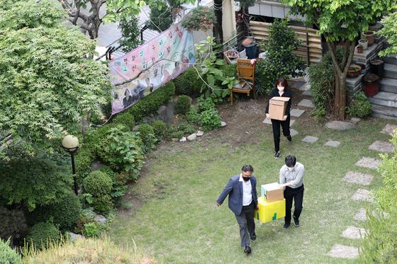 정의기억연대(정의연)를 수사하는 검찰이 지난달 21일 서울 마포구 위안부 피해자 할머니들의 쉼터 '평화의 우리집'에서 압수 수색을 마치고 물품을 들고 차량으로 향하고 있다. 뉴스1