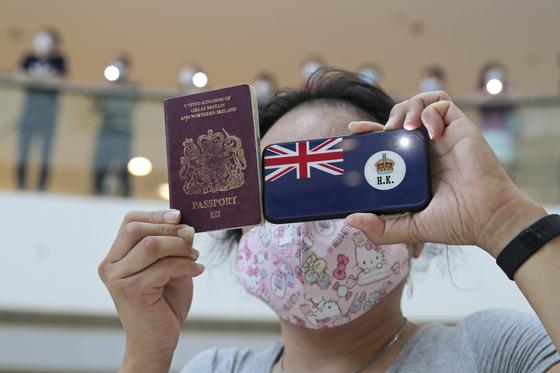 지난달 29일 홍콩의 한 쇼핑몰에서 한 홍콩 시민이 과거 영국 식민지 시절 사용되던 홍콩 여권과 홍콩 국기모양의 스마트폰 케이스를 들고 있다.[AP=연합뉴스]