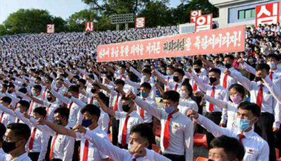 북한 청년들이 탈북자들의 대북전단 살포를 절대 용납할 수 없다고 성토하는 군중집회를 열었다고 노동신문이 7일 보도했다. 사진은 평양시 청년공원 야외극장에 모인 북한 학생들이 마스크를 쓴 채로 주먹을 불끈 쥐고 군중집회를 하는 모습.[연합뉴스]