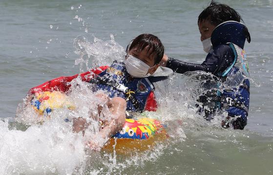 전국적으로 30도를 웃도는 무더위가 찾아온 7일 오후 부산 해운대해수욕장을 찾은 어린이들이 코로나19 예방을 위해 마스크를 착용한 채 물놀이를 즐기고 있다. 송봉근 기자