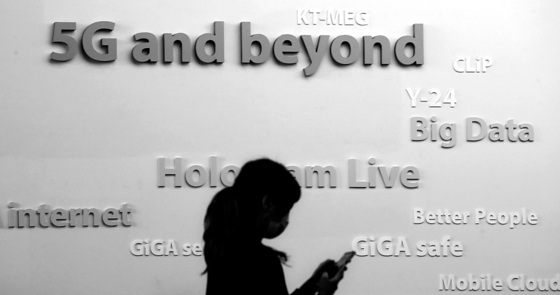 2일 서울 세종대로 광화문 KT스퀘어에서 5G 관련 문구가 새겨진 벽면 앞으로 한 시민이 스마트폰을 사용하며 지나가고 있다. 연합뉴스