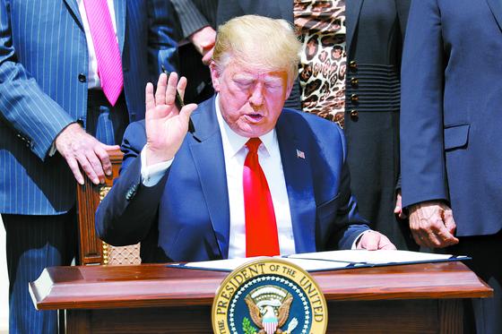 도널드 트럼프 미국 대통령이 5일 백악관에서 법안에 서명하고 있다. 기자들 질문이 이어지자 질문을 받지 않겠다는 뜻을 나타냈다. [EPA=연합뉴스]