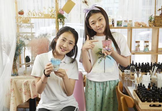 안효빈(왼쪽)·박성경 학생모델이 각자 만든 수제 젤 캔들을 들고 포즈를 취했다.
