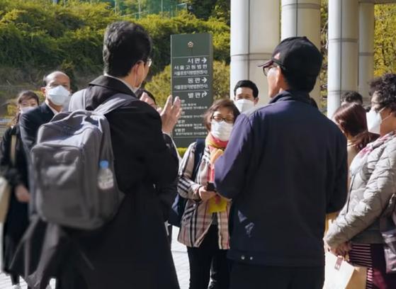 법원 앞에서 피해자들과 이야기를 나누는 김선웅 전 이사. [유튜브 캡처]