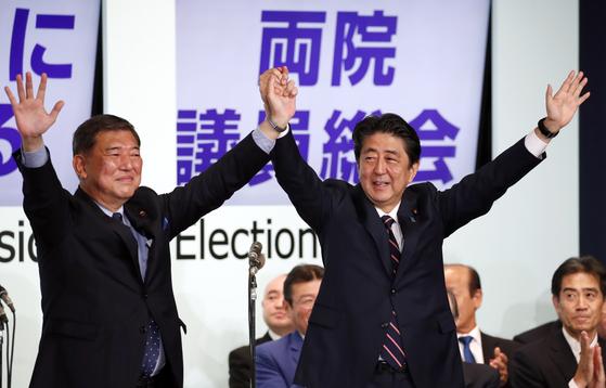 지난 2018년 9월 자민당 총재 경선에서 3연임에 성공한 아베 신조 총리와 경쟁자였던 이시바 시게루 전 간사장이 함께 인사를 하고 있다. [EPA=연합뉴스]