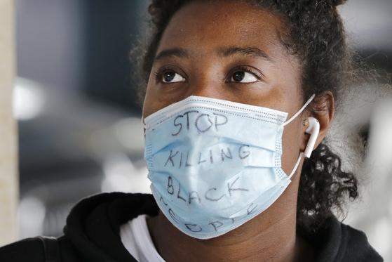 세계보건기구가 미국서 촉발된 시위 중에도 마스크를 써달라고 당부했다. 사진은 지난 8일 미국서 한 여성이 흑인을 죽이는 것을 중단하라고 적힌 마스크를 착용하고 있다. [AP=연합뉴스]
